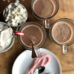 Cocoa for a crowd with peppermint sticks, marshmallows and whipped cream
