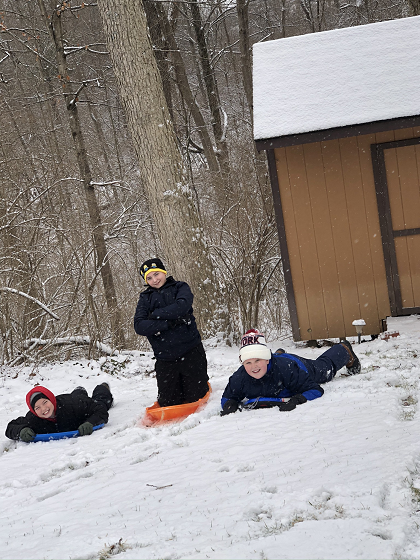 Noah & Co outside on sleds