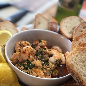 Garlic Chili Shrimp in bowl with lemon wedges and baguette slices.