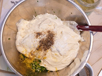 Metal mixing bowl with mayo and tartar ingredients, waiting for spatula to stir it together.