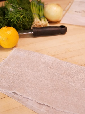 Towel to put under cuttingboard - with lemons, herbs and zester.