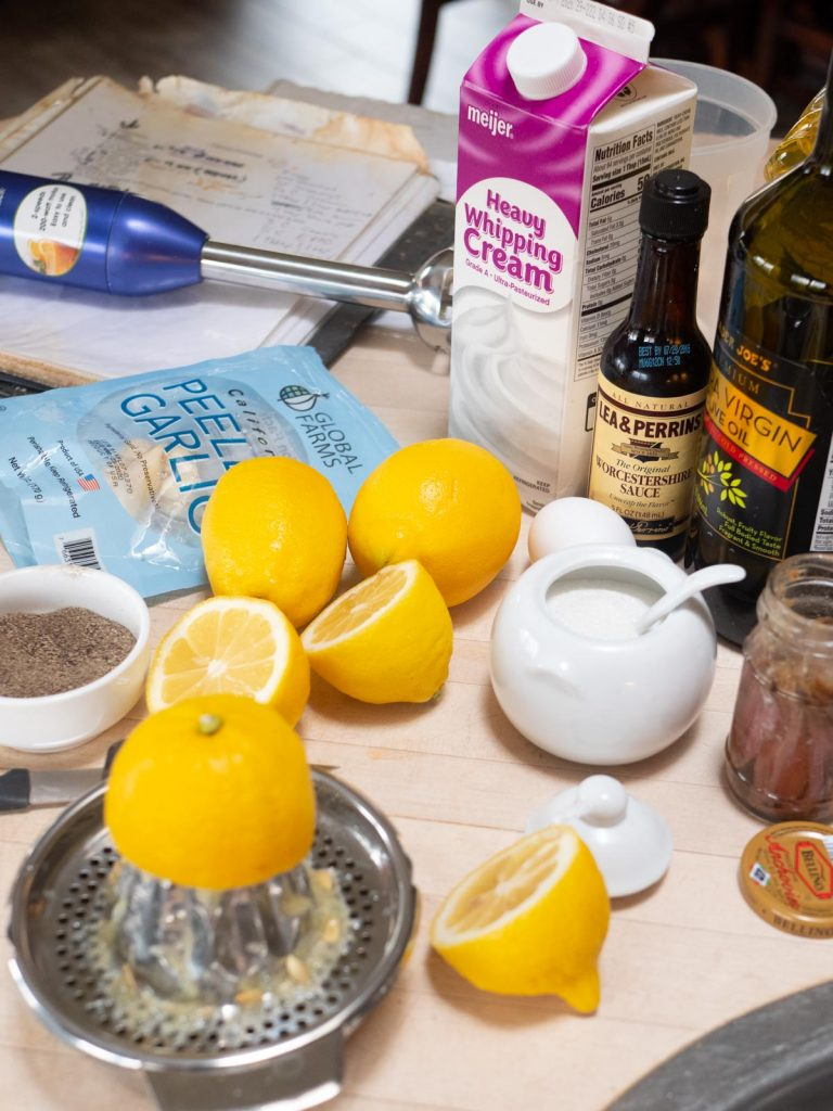 Ingredients for Caesar dressing - lemons, garlic, cream, olive oil, anchovies