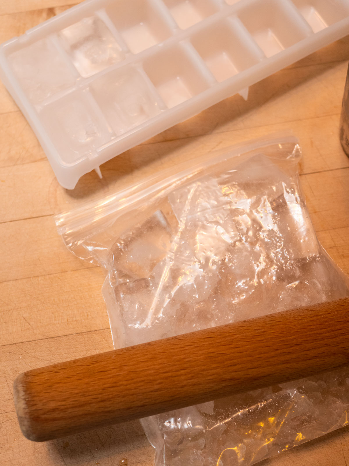 Bag of ice with ice tray and rolling pin to crush