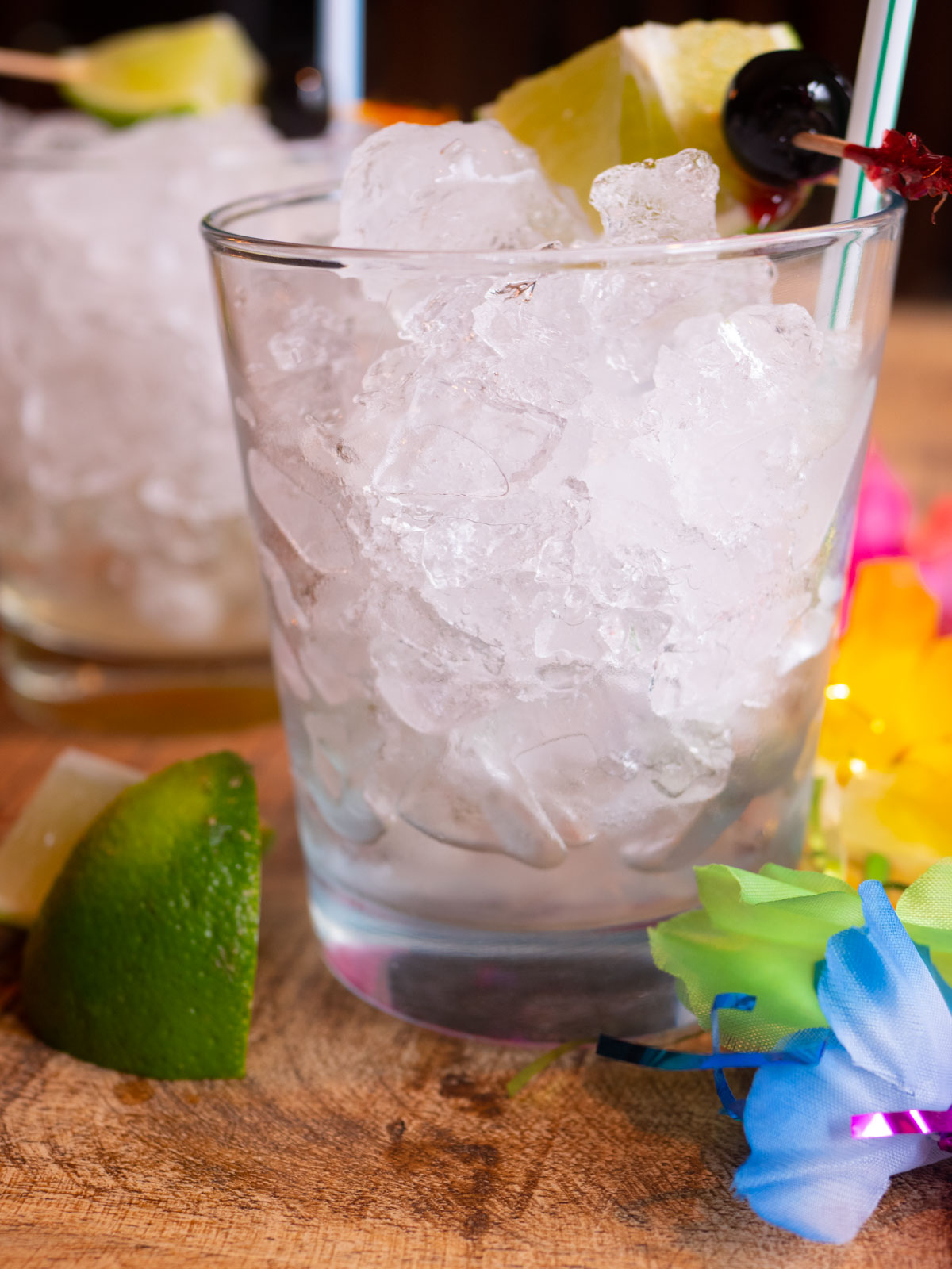 Glasses with ice, mai tai garnish and lime