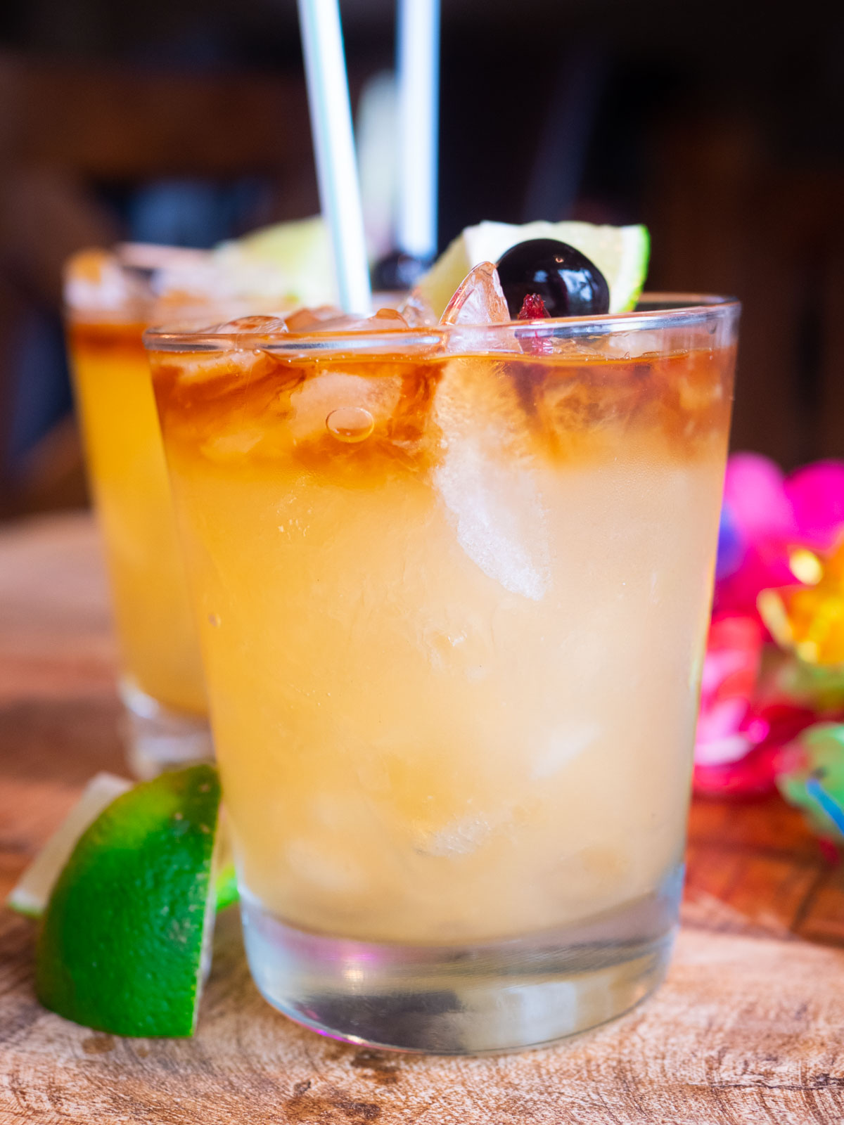 Mai Tai in glasses with lime and straw and lei