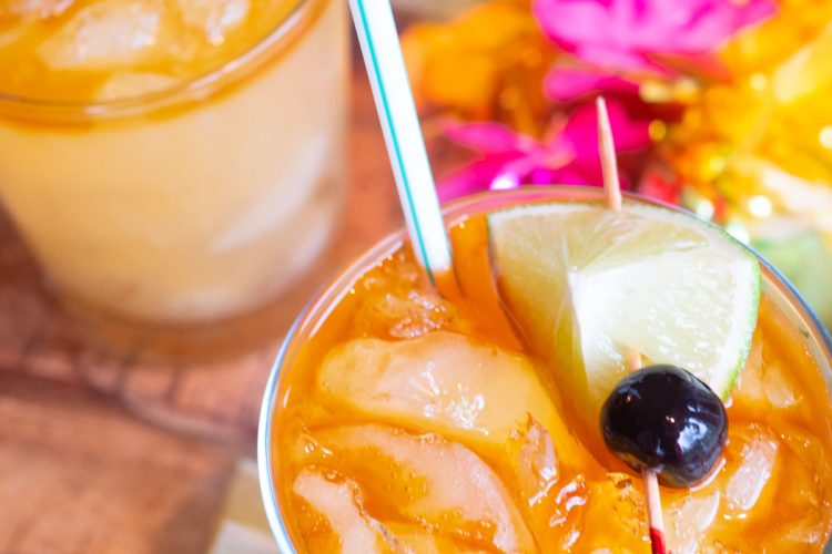 Mai Tais in glasses with lei and limes